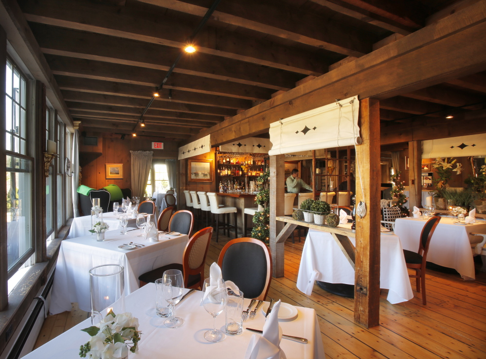 The dining areas of On the Marsh Bistro in Kennebunk are decorated with upholstered furniture, ornate wooden chandeliers, patterned pillows and oil lamps on every table.