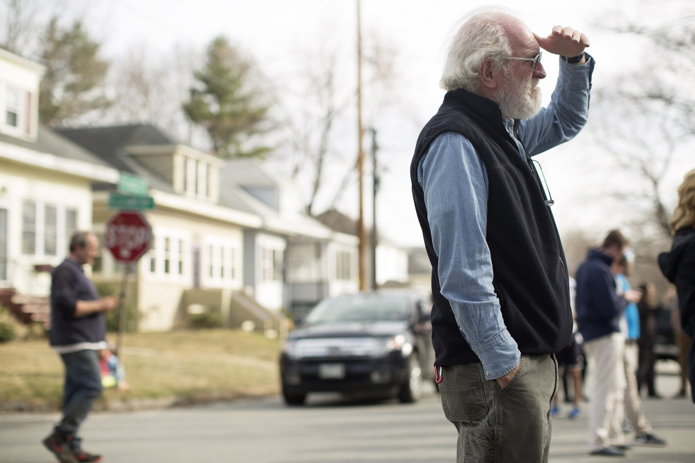 John Murton, who has lived in the neighborhood for 35 years, watches as police gather outside an Elizabeth Road house after a shooting Friday. Yoon Byun/Staff Photographer