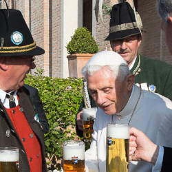 Pope Emeritus Benedict XVI toasts his 88th birthday Thursday with Monsignor Georg Gaenswein, right, and members of a group from his hometown region in Bavaria.