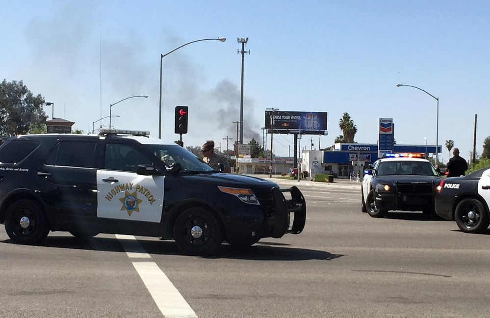 Highway patrol officers block off Herndon Avenue at Highway 99 after a natural gas explosion in Fresno, Calif., on Friday. Smoke from the fire can be seen in the background.