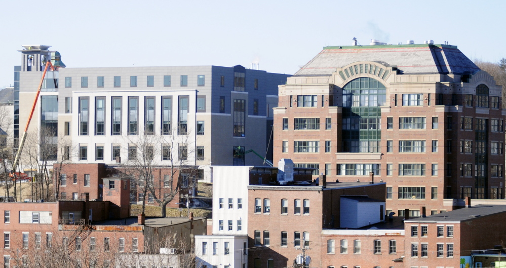 The Key Bank building on Water Street in Augusta looms above the other buildings downtown. A state proposal to move state departments out of the building could leave all but one floor vacant, city officials say. The new Capital Judicial Center, left, is on a hill above downtown.