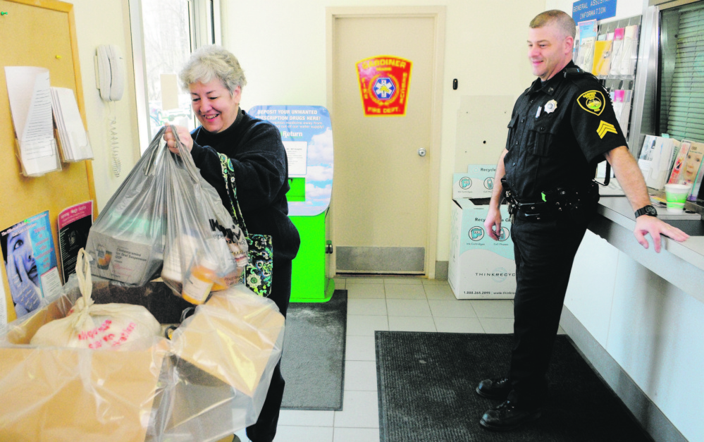 Carmen McCurdy, left, chats with Gardiner Police Sgt. Todd Pillsbury as she drops of medicine during the annual drug take-back at the Gardiner police station in 2013. Sheriff departments across Maine are taking over the event as the DEA says it can't fund the event.