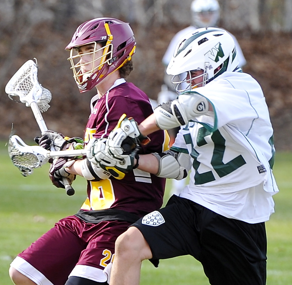 Finn Raymond, left, of Cape Elizabeth is held back by Cooper Chap of Waynflete while looking to pass Friday during their season-opening boys' lacrosse game in Portland. The Capers won, 18-6.