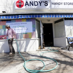 Sean Ireland, one of the new owners of the former Andy's Handy Store in Yarmouth, cleans the sidewalk in front of the building where Otto Pizza will locate along with two other businesses. The store's interior has been gutted for rehabilitation.