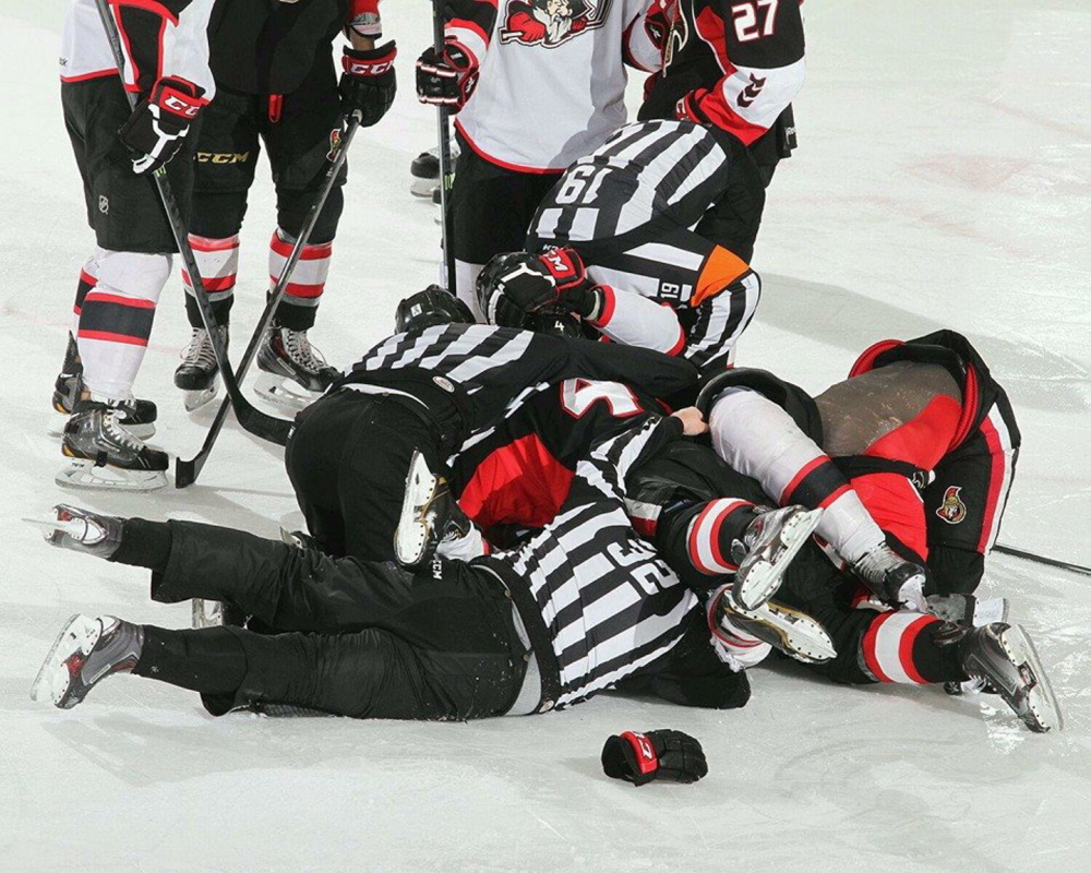 Linesman Joe Andrews, No. 32, is buried in a scrum during a Portland Pirates game. Andrews is known for having a rapport with players and coaches.