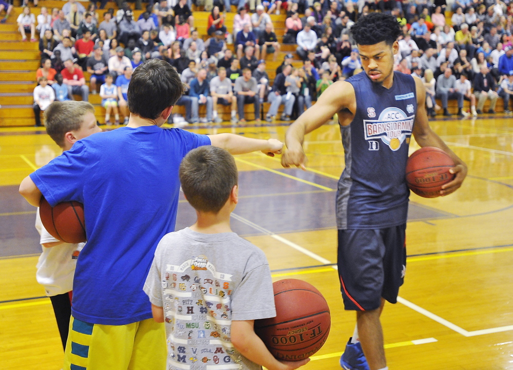 Bode Meade, 12, of Gorham receives a fist bump to remember from Quinn Cook of Duke. A team of Atlantic Coast Conference seniors that tours North Carolina high schools each spring made its first-ever Maine appearance and was greeted by a packed gym at Deering High. Gordon Chibroski/Staff Photographer