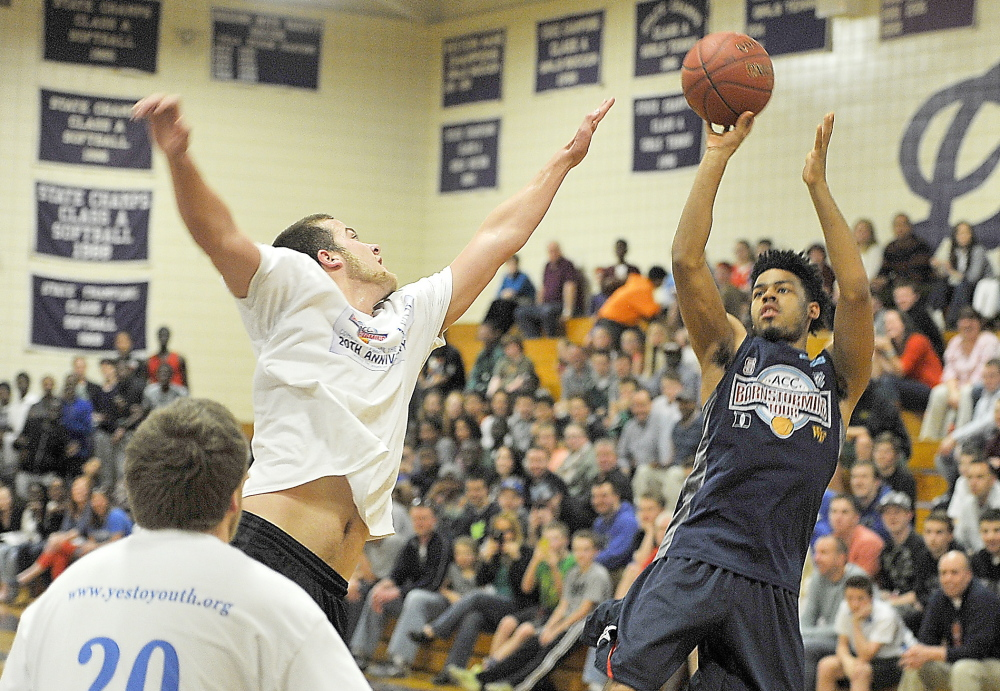 Quinn Cook, the point guard who helped Duke win the NCAA championship earlier this month and the school's career assists leader, lofts a 3-pointer over Kevin Barrett of Thornton Academy. A team of Atlantic Coast Conference players put on an exhibition Friday night at Deering High against a team of southern Maine high school players. Gordon Chibroski/Staff Photographer