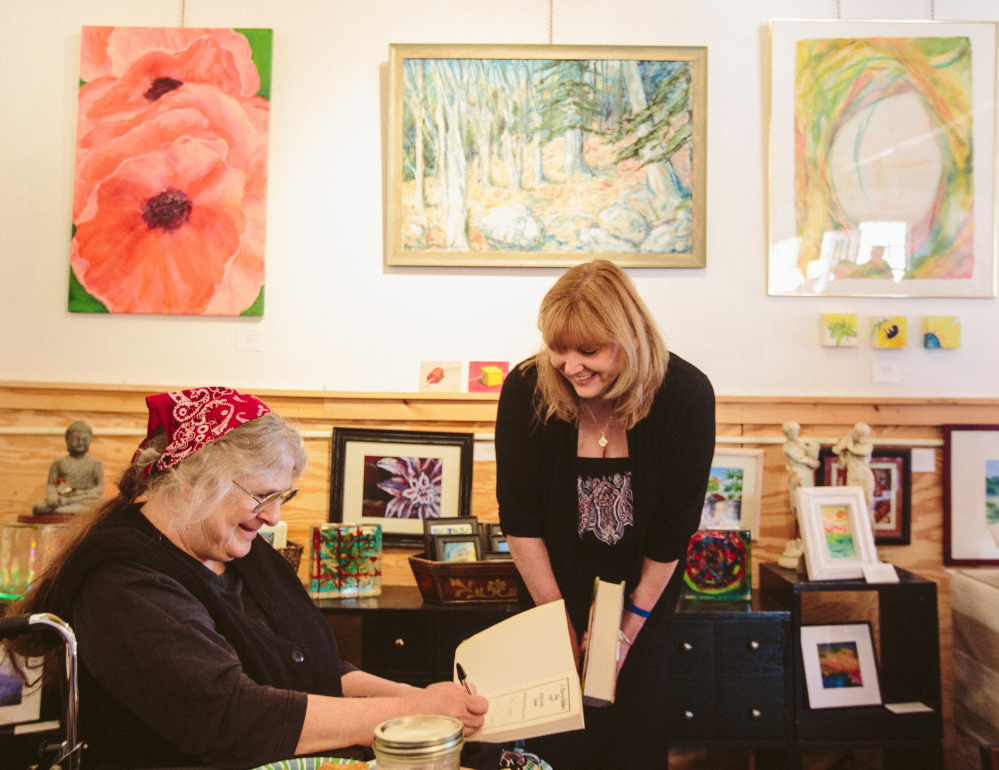 Carolyn Chute signs a book Saturday for Carmel Curran Blanchette of Framingham, Mass., at the Blackbird Gallery and Studio in North Berwick.