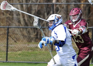 Luigi Grimaldi of St. Joseph's College gets checked by Norwich's Thomas Carlson as Grimaldi heads toward the goal in a men's lacrosse game Saturday at Deering High. Norwich won, 9-3.