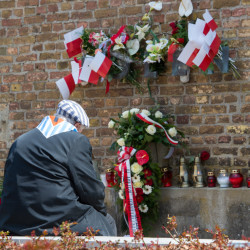 A Nazi concentration survivor from Poland sits at the 'Wall of Nations' in front of the word 'Polen' (Poland), adorned with flowers and flags, at the Ravensbrueck concentration camp memorial site during the memorial  ceremonies marking  the 70th anniversary of the camp's liberation in Fuerstenberg, Germany, on Sunday.