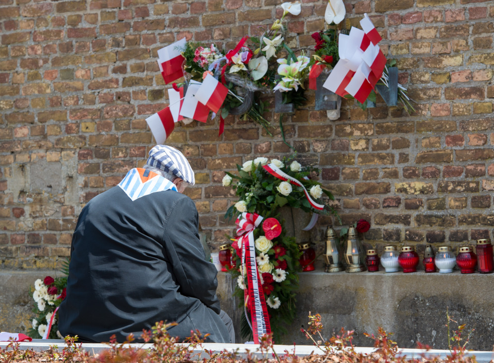 A Nazi concentration camp survivor from Poland sits at the Wall of Nations in front of the word 'Polen' (Poland), adorned with flowers and flags, at the Ravensbrueck memorial site during ceremonies marking  the 70th anniversary of the camp's liberation in Fuerstenberg, Germany, on Sunday.