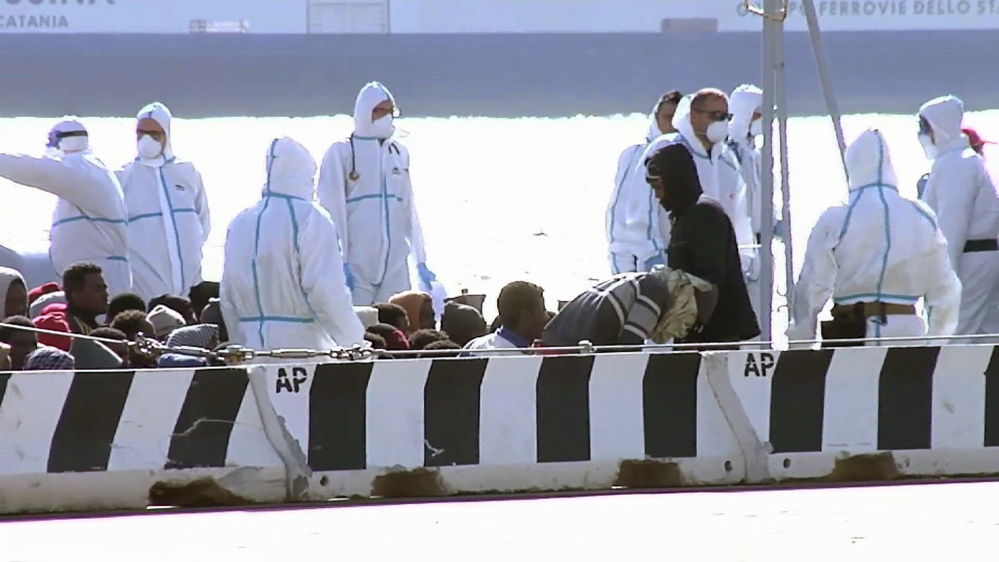 Migrants are seated, surrounded by emergency relief workers aboard a vessel at the Italian port of Messina on Saturday as migrants prepare to be processed.