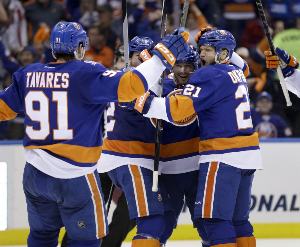 New York Islanders' Kyle Okposo, right, celebrates with teammates after scoring in the second period Sunday in Uniondale, N.Y.