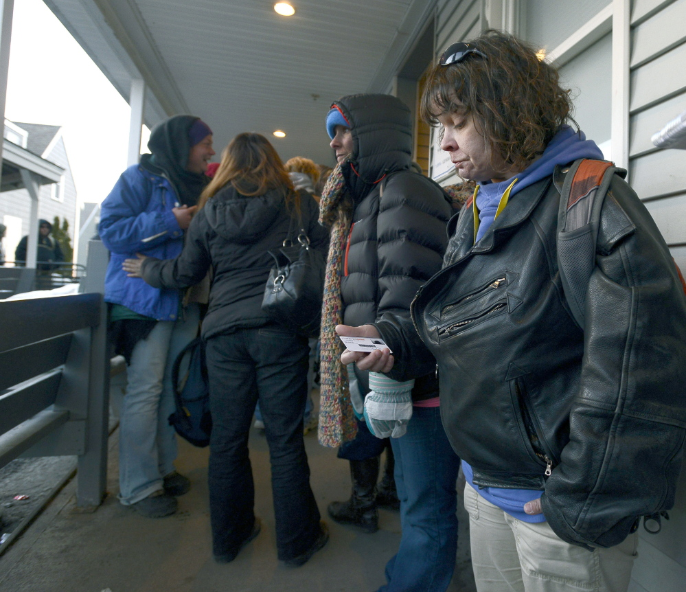 Lori Godin holds her shelter ID card March 12 as she waits in line to spend the night at the Oxford Street Shelter in Portland. She is working full time at a South Portland hotel and trying to build up some savings.