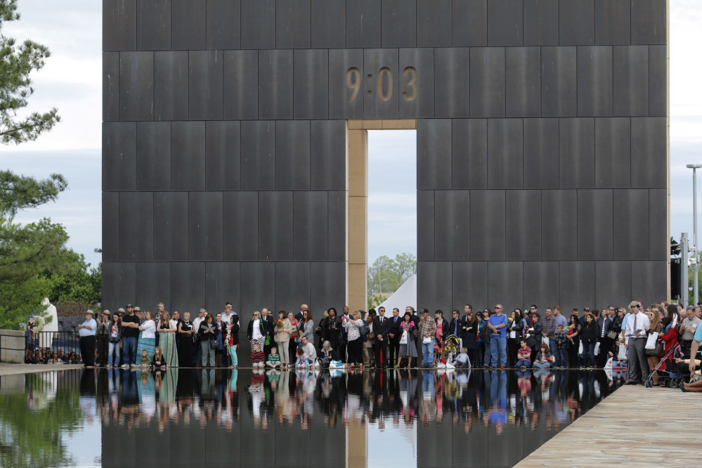 People gather at the end of the reflecting pool near the 9:03 Gate during a remembrance ceremony Sunday at the Oklahoma City National Memorial & Museum in Oklahoma City. Twenty years ago, a terrorist bombing there killed 168 people and injured many others.