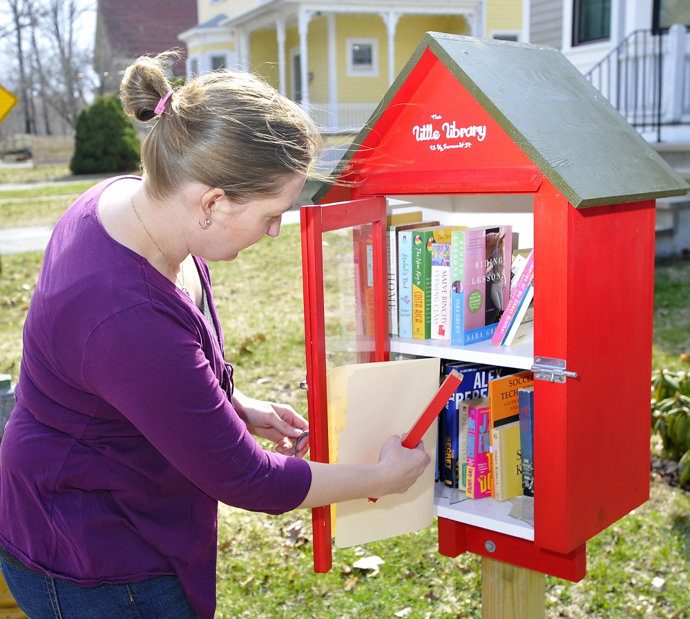Bethany Hundt looks at the damage to the Little Free Library, which her father built, in her front yard on Summit Street in South Portland.