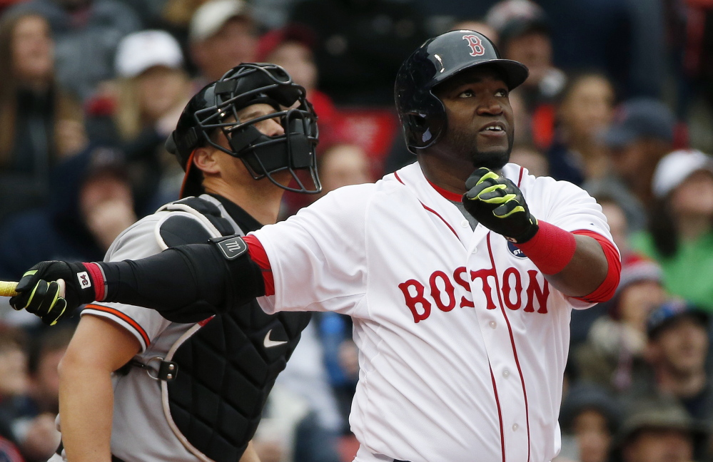Boston's David Ortiz watches his sacrifice fly in front of Baltimore Orioles' catcher Ryan Lavarnway during the first inning in Boston on Monday.