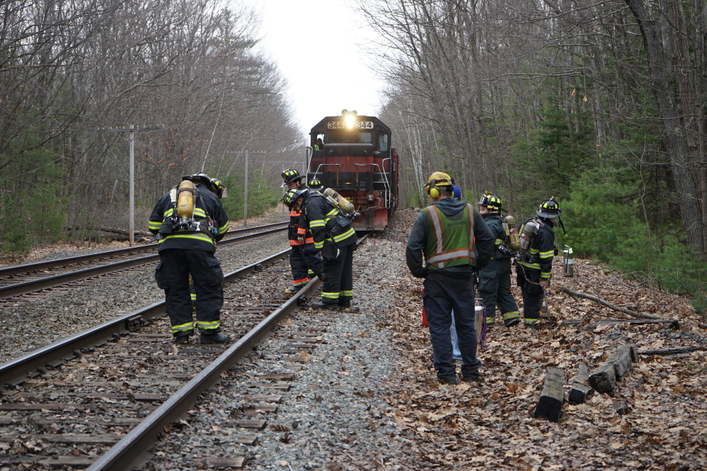 Scarborough firefighters and Pan Am Railways crew members inspect the railway off Chamberlain Road in Scarborough around 1:40 p.m. Monday.