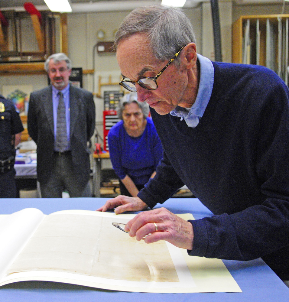 Hallowell City Historian Sam Webber looks at the writing on the back of the city's 1776 copy of the Declaration of Independence at the Maine State Museum in Augusta.