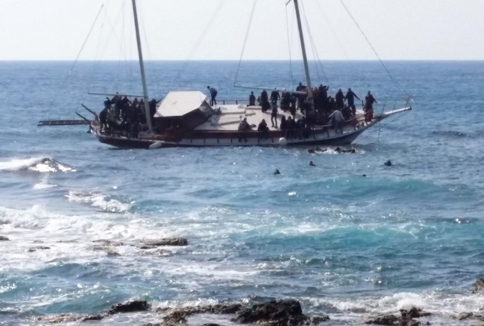 Migrants swim to reach the shore as others remain on a listing vessel that later sank in the Aegean sea near the island of Rhodes, Greece on Monday.