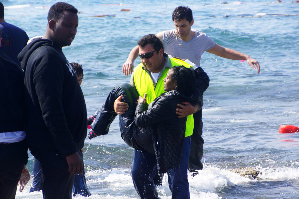 A man rescues a migrant from the Aegean Sea on Monday. Greek authorities said at least three people have died, including a child, after a wooden boat ran aground.