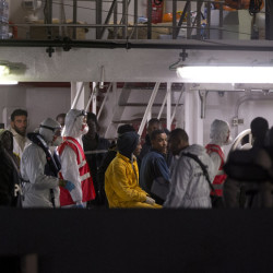 Survivors of the boat that overturned off the coast of Libya Saturday wait to disembark from Italian Coast Guard ship Bruno Gregoretti, at Catania Harbor, Italy, on Monday.