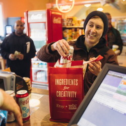 "Morgan McCormack places soda into a reusable bag at Hilltop Superette on Congress Street on Monday. McCormack says she brought reusable bags to the store prior to the city's new policy, but the new fee is ""definitely a reminder."""