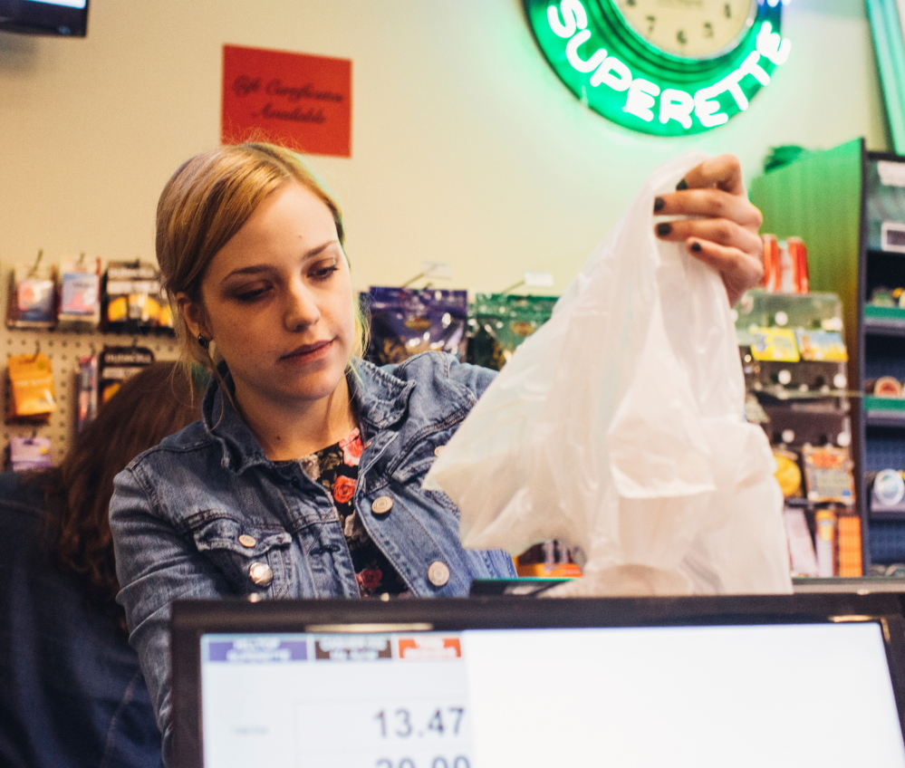 Hilltop Superette cashier Ayriel Chase prepares a plastic bag for a customer. Some shoppers carry items out in their hands to avoid a fee.
