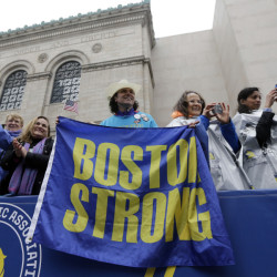 "Carlos Arredondo, a 2013 Boston Marathon first-responder, holds a ""Boston Strong"" banner beside his wife, Melida, right, in the grandstand near the Boston Marathon finish line."