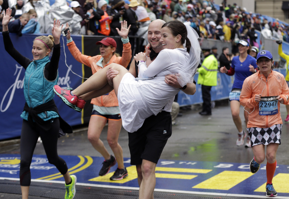 Ross Cockerham carries Ansley Proctor over the finish line after they ran the Boston Marathon on Monday. The couple from Columbia, Md., are set to be married Saturday.