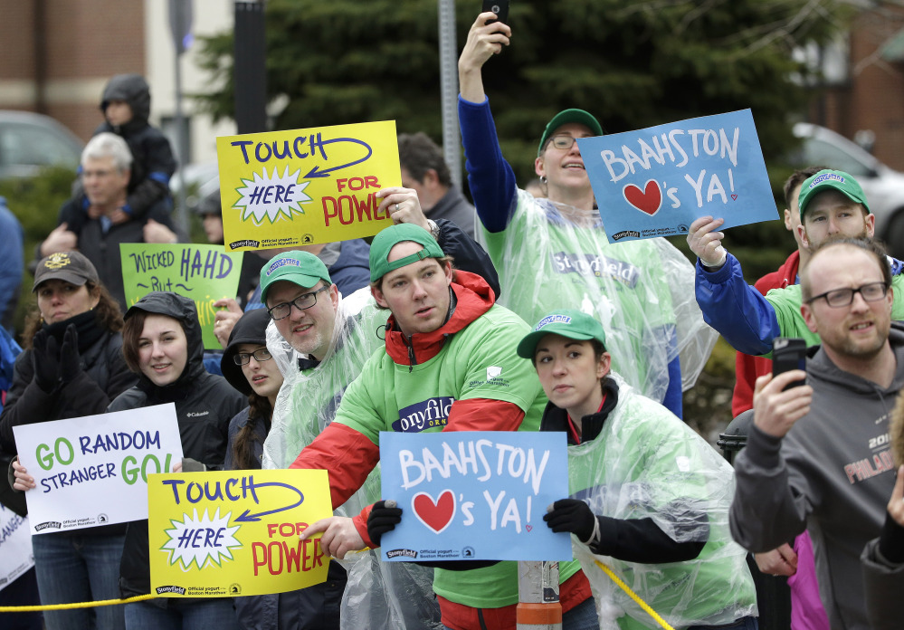 Spectators in Natick, Mass., display placards to runners in the Boston Marathon.