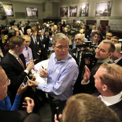 "In this April 17, 2015, photo, former Florida Gov. Jeb Bush, center, mingles at a ""Politics and Eggs"" event, a breakfast fixture for 2016 presidential prospects at Saint Anselm College in Manchester, N.H."
