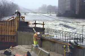 A construction crew works on a bridge alongside a raging Saccarappa Falls on the Presumpscot River in Westbrook after heavy rains in the spring. Sappi Fine Papers has  selected a plan for a fish passageway at the falls.