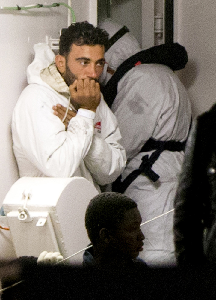 Mohammed Ali Malek, one of the survivors of the boat that overturned off the coast of Libya on Saturday, waits to disembark from Italian Coast Guard ship Bruno Gregoretti, at Catania Harbor, Italy, on Monday. He was among those taken into custody by Italian police on suspicion of being a crew member aboard a smuggler's boat.