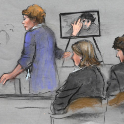 In this courtroom sketch, prosecutor Nadine Pellegrini makes opening arguments during the first day of the penalty phase in the trial of Boston Marathon bomber Dzhokhar Tsarnaev, seated at right, Tuesday in federal court in Boston. Pellegrini displayed a photo to the jury of Tsarnaev extending his middle finger to a security camera taken in his jail cell three months after the attack.
