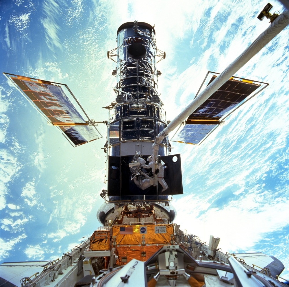 Astronauts Steven L. Smith and John M. Grunsfeld work on the Hubble during a servicing mission in 1999. NASA marks the orbiting telescope's 25th anniversary on Friday.