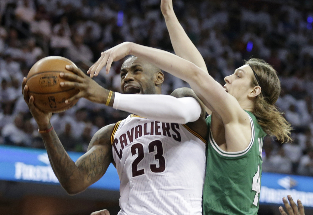 Cleveland Cavaliers' LeBron James, left, drives to the basket against Boston Celtics' Kelly Olynyk during the fourth quarter of a first-round playoff game Tuesday in Cleveland.  The Associated Press
