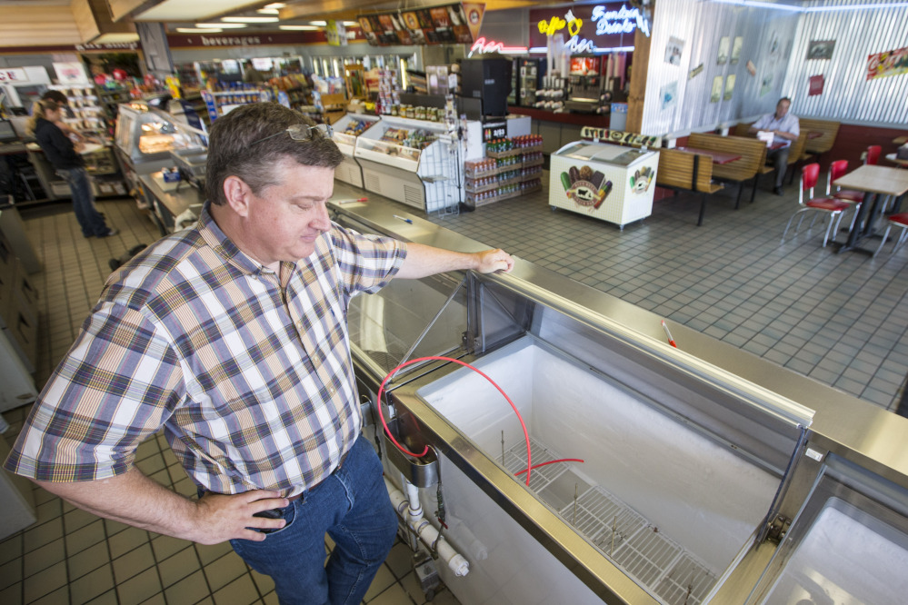 Brett Smith, owner of Scoops Ice Cream, looks over the empty ice cream case on Tuesday in Brenham, Texas.