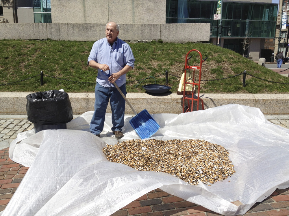Mike Roylos, owner of the Spartan Grill, shows a pile of cigarette butts that were collected in SideWalk Buttler receptacles in Monument Square in Portland. Roylos held the demonstration on Earth Day to call attention to local clean-up efforts.