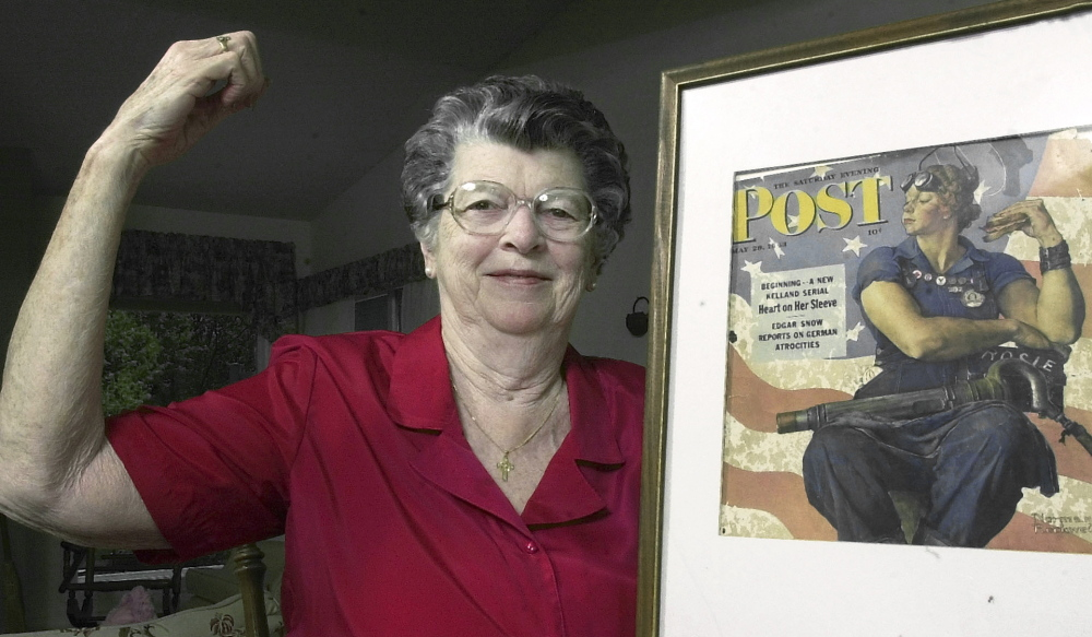 In a 2002 photo,  Mary Doyle Keefe poses with the iconic 1943 cover of the Saturday Evening Post for which she  modeled as Rosie the Riveter in the Norman Rockwell painting.