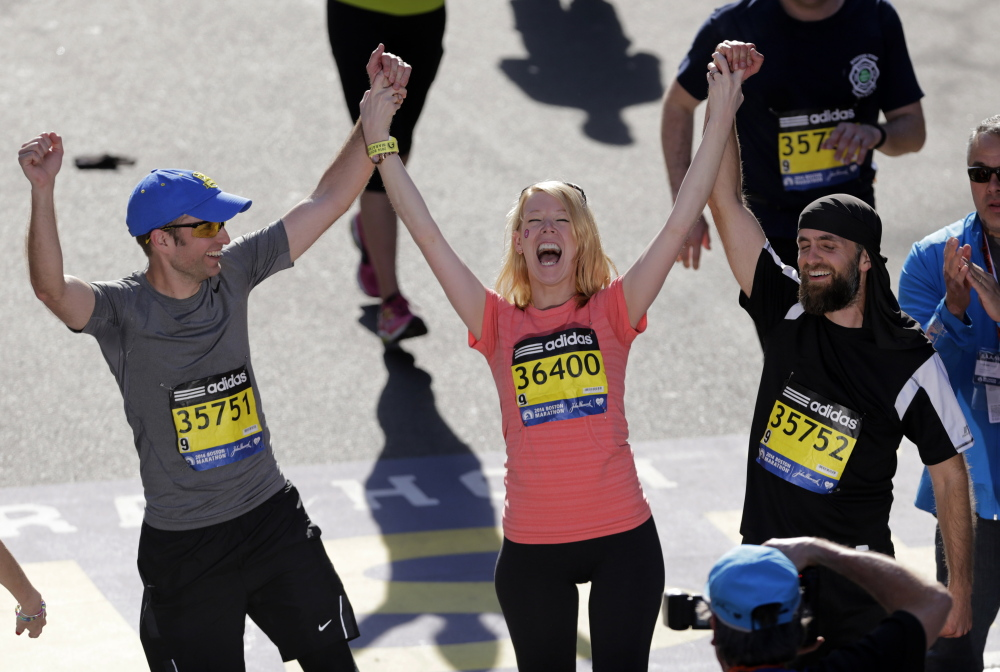Timothy Haslet, left, and David Haslet, right celebrate with their sister Adrianne Haslet-Davis as she crosses the finish line of the 118th Boston Marathon Monday, April 21, 2014 in Boston. Haslet-Davis, a professional dancer, lost her lower left leg at last year's marathon when one of two bombs exploded as she watched runners near the finish line. (AP Photo/Charles Krupa)