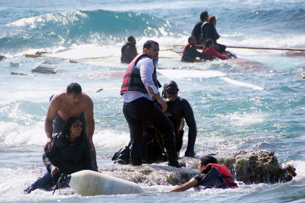 Migrants seek safety in the Aegean Sea island of Rhodes on Monday after their wooden boat sank, killing at least three people, including a child.