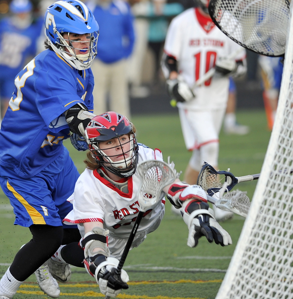 Sam Neugebauer dives and puts the ball in the goal, but it did not count because he was in the crease. Neugebauer had three goals and an assist for Scarborough, which lost 11-10 in boys' lacrosse to Falmouth on Wednesday.