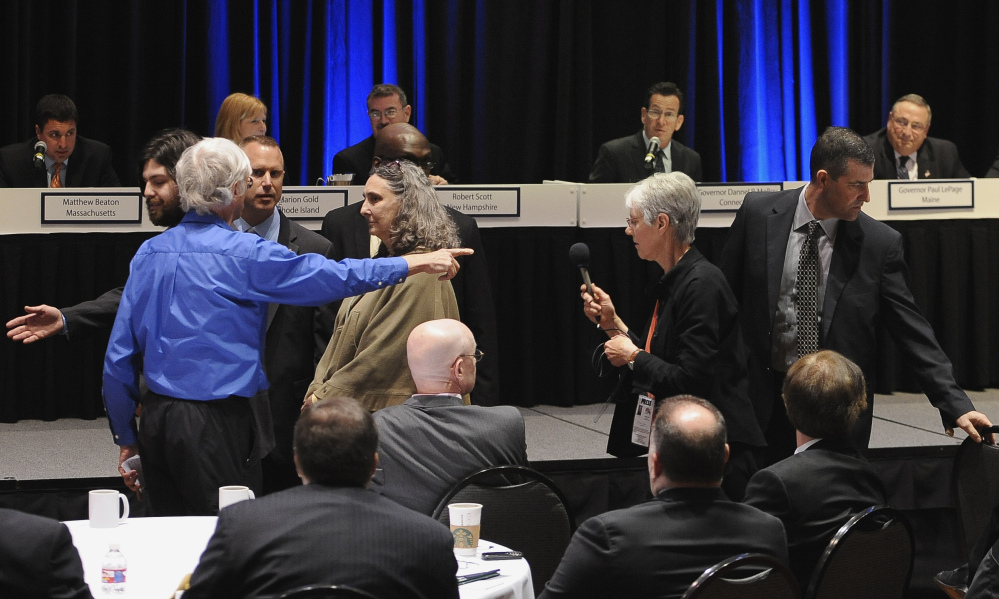 David Ludlow of Boston's Jamaica Plain neighborhood, in blue on left, stands up to protest before he is escorted out by security as Connecticut Gov. Dannel P. Malloy and Maine Gov. Paul LePage, top right, listen during a panel meeting, Thursday, April 23, 2015, in Hartford, Conn. Ludlow accused the governors of indifference to climate change in an energy policy that increasingly relies on natural gas and efforts to build more fossil fuel pipelines.