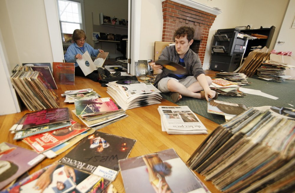 Zach Lapierre, right, a freshman at the University of Southern Maine and a work-study student at WMPG, and Jessica Lockhart, a WMPG volunteer who teaches radio production, help to stack record albums in newspaper after a broken water pipe caused a flood in its studios Wednesday night in Portland.