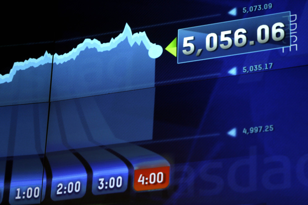 Market data is displayed on the screens at the Nasdaq MarketSite in New York on Thursday. The Nasdaq composite has closed at a record high for the first time since the dot-com bubble of 2000.