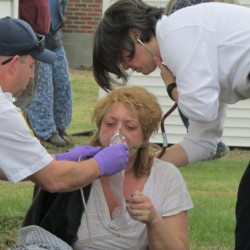 Christie Mann is treated for possible smoke inhalation after being pulled to safety from her Winslow apartment Thursday.