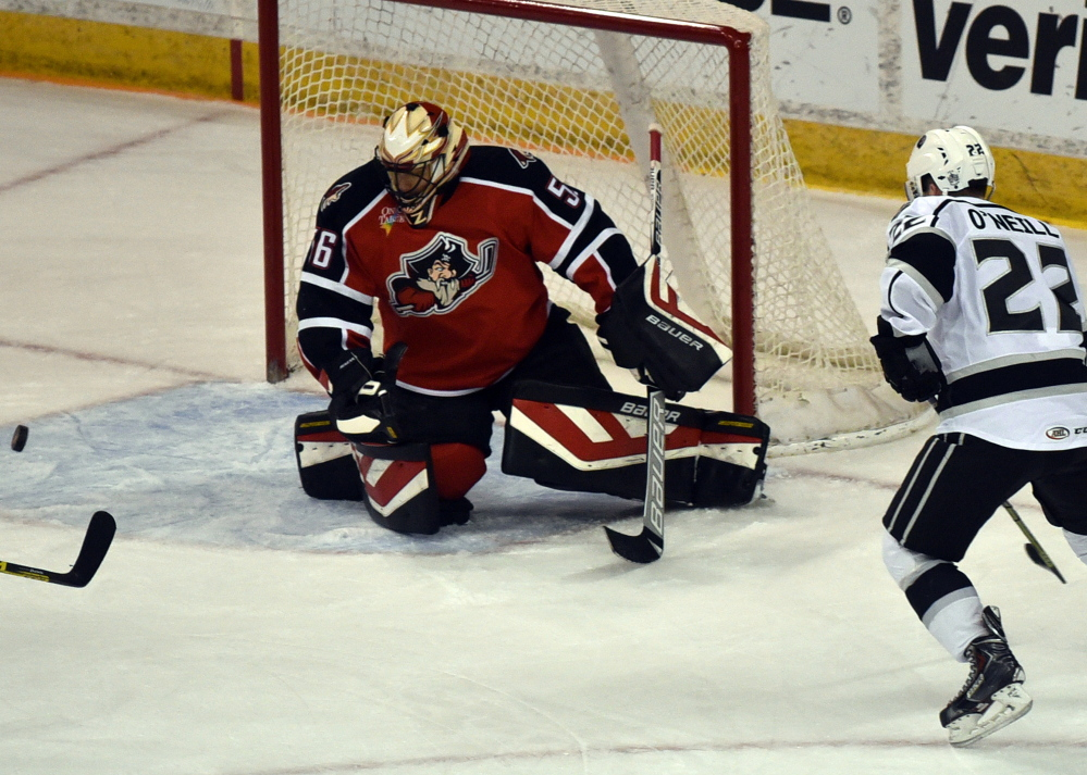 Brian O'Neill of the Manchester Monarchs watches a shot leading to his goal, the fourth of the game against Portland goalie Mike McKenna at the Verizon Wireless Arena in Manchester on Thursday.
