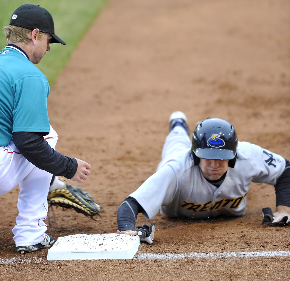 Jake Cave of the Trenton Thunder gets back to first as Michael Brenly of the Portland Sea Dogs reaches to apply a tag during a pickoff attempt Thursday night.