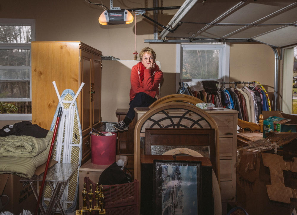 FALMOUTH, ME - APRIL 23: Lisa Arens sits atop items for her yard sale, which she had to bring inside her garage after it began raining in Falmouth, ME on Thursday, April 23, 2015. Arens and her husband are moving to Lake Worth, Florida. (Photo by Whitney Hayward/Staff Photographer)